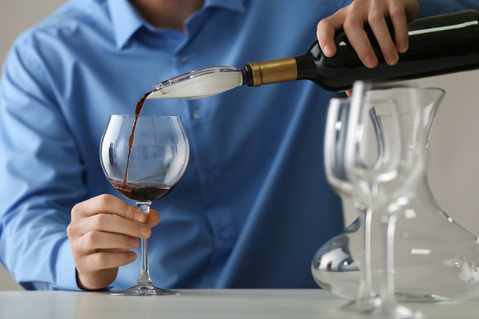 Sommelier pouring red wine into glass